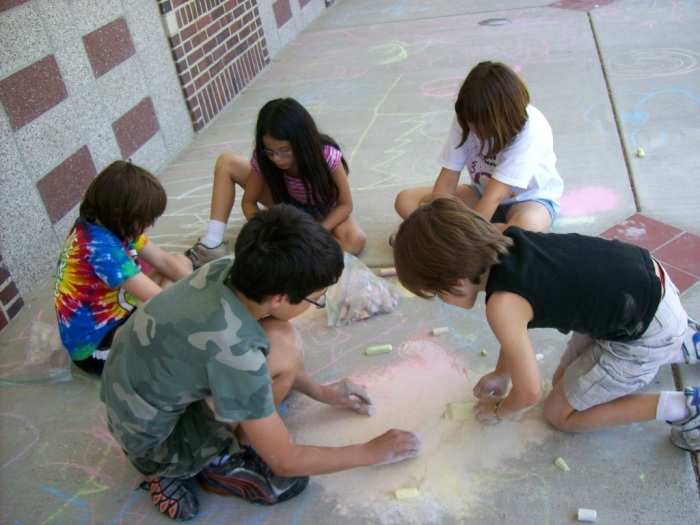 Kids working on a chalk drawing